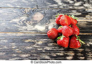 Strawberry on a dark wooden background.