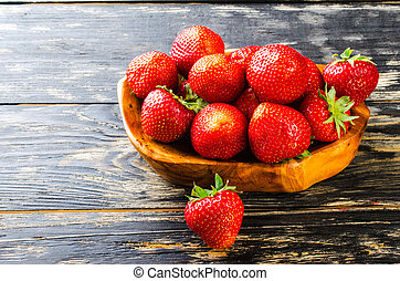 Strawberry on a dark wooden background.