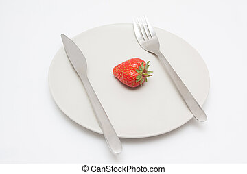 Strawberry on plate with knif and fork