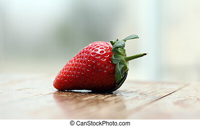 Strawberry on wooden vintage table near the window