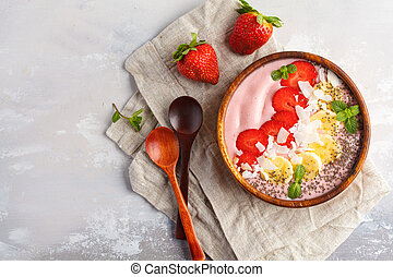 Strawberry pink smoothie bowl with banana, coconut and chia seeds, top view. Healthy vegan food concept.