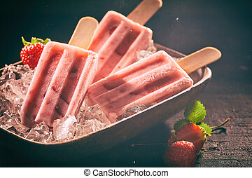 Strawberry Popsicles in vintage scene with scratches and dust. For summer ice cream advertising.