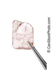 Strawberry quartz jewel stone texture in tweezers on white light isolated background. Macro closeup.