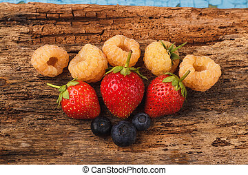 Strawberry, raspberry and blueberry on the old wooden board