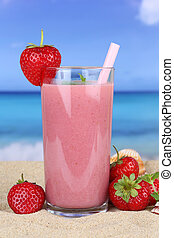 Strawberry smoothie fruit juice cocktail with strawberries fruits on the beach