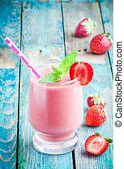 strawberry smoothie in a glass with a straw