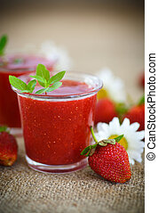 strawberry smoothie in a glass with strawberries on a table