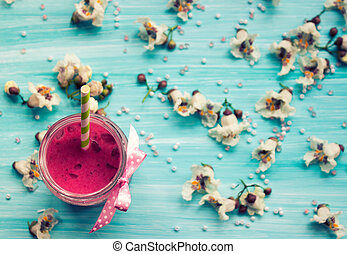 Strawberry smoothie on blue background with flowers