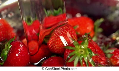 Strawberry with leaves close up under running jets of water...