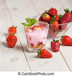 Strawberry yogurt and granola in glass