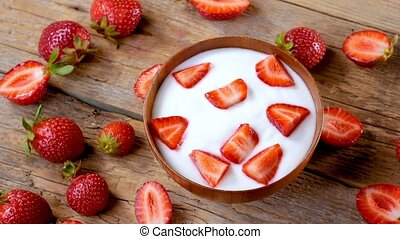 Strawberry yogurt in wood bowl spinning on table -...