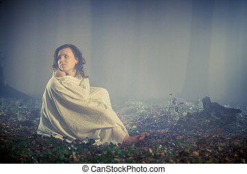 Stray woman wrapped in a white sheet in a misty forest