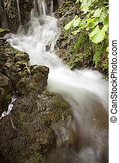 Stream blurred water in small waterfall