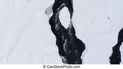 Stream flowing on snowy area during winter 4k - Aerial of...