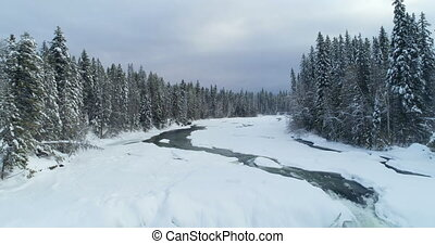 Stream flowing through snowy forest 4k - Stream flowing...