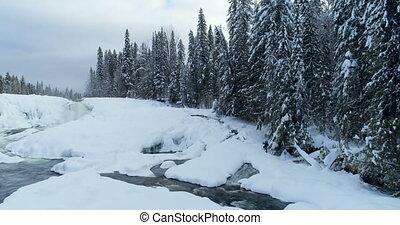 Stream flowing through snowy forest 4k - Stream flowing...