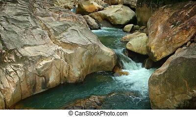 Stream forms small waterfalls between rocks.
