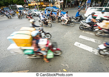 Stream of bikes in busy street in Vietnam. - Motion view of...