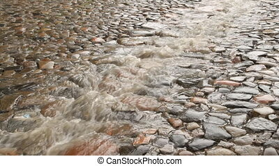 Stream of rain on the cobble road