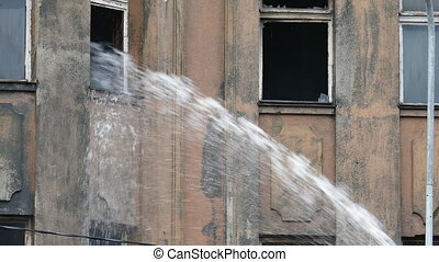 Stream of water from a fireman's hose eliminates a fire in...