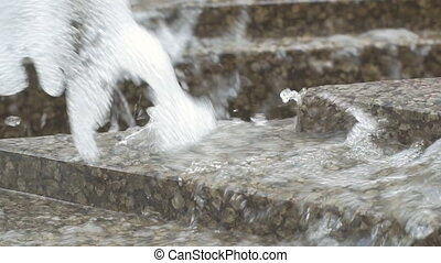Stream of water from the fountain on the granite