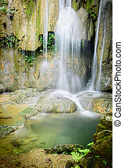 White current stream gushing through cascade tiers into emerald pond at Thac Voi waterfall of tropical rainforest in Thanh Hoa province, Vietnam. Natural background.