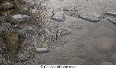 stream small mountain river in winter season over stones and...