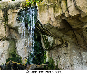 streaming waterfall in a mountain scenery, nature background