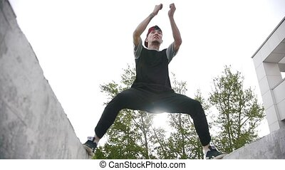Street acrobatics - teenager jumps a back flip among concrete structures slow motion