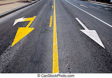 White and yellow arrows on the street