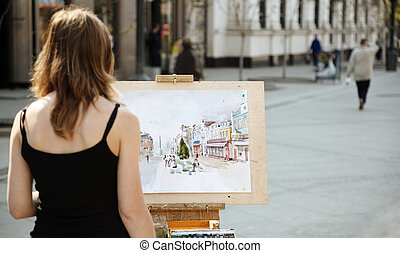 street artist - young woman painting outside, focus point on...