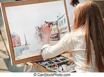 young woman painting outside, focus point on hand (selective)