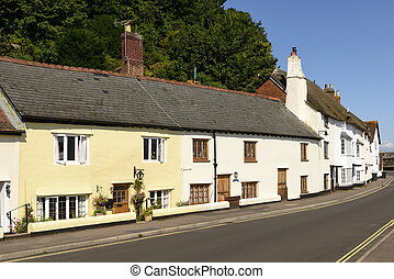 view of medieval cottages built with stone prospecting on a street just in front of sea in historic touristic village of Somerset. Shot in bright light