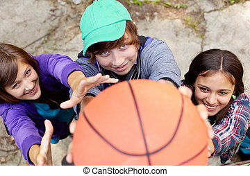 Cheerful teens playing basketball in the street holding the ball close to the camera