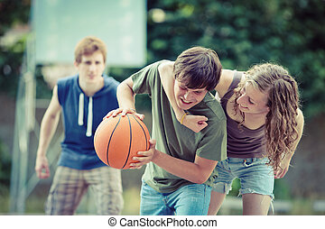 Street basketball - Teens playing a game of basketball on an...