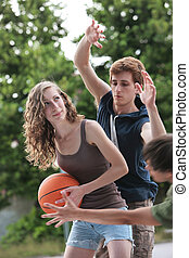 Street basketball - Two boys and a girl playing a game of...