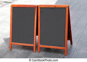 Empty blackboards in wooden frames on street