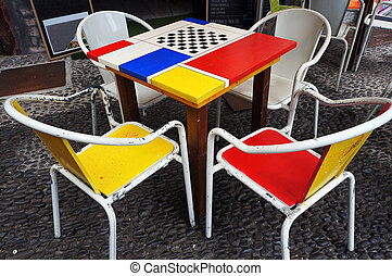Tables and chairs of street cafe in Funchal, Madeira.