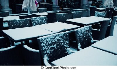 Street cafe tables in the snow. Low season concept. 4K steadicam video