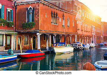 Street canal in Murano island, Venice. Narrow canal among old colorful brick houses in Murano, Venice. Murano postcard, Venice, Italy.