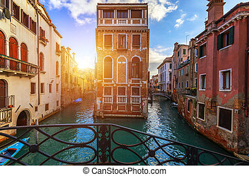 Street canal in Venice, Italy. Narrow canal among old colorful brick houses in Venice, Italy. Venice postcard