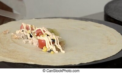 Street chef wraps a pancake in a fast food restaurant in slow motion
