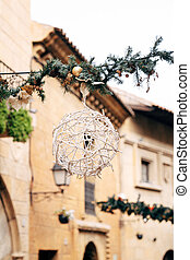 Street Christmas decoration of houses - a ball of garlands on a Christmas tree branch.