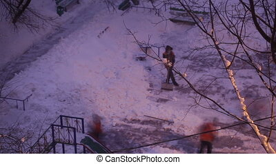 Street cleaners in orange uniform removing the snow. Time lapse. Wide high angle shot.
