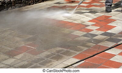 Man worker cleaning city dirty streets with high pressure...