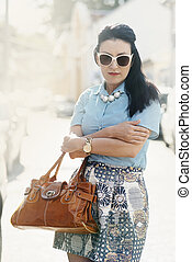 Pretty woman in stylish fashionable clothes and luxury leather bag