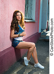 street fashion of contemporary youth girl.sexy brunette girl with sporty body wearing jeans shorts