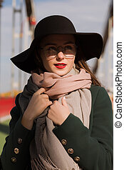 Street fashion portrait of attractive young model walking at the city. Woman wearing fashionable hat, scarf and glasses