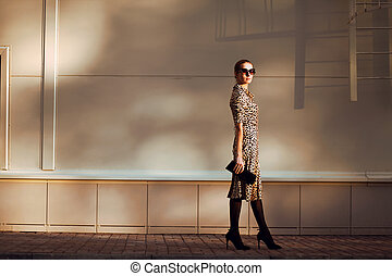 Street fashion, pretty elegant woman model in leopard dress and