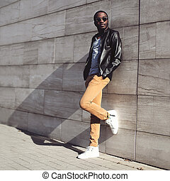 Street fashion, stylish young african man wearing a sunglasses and black leather jacket on evening city background